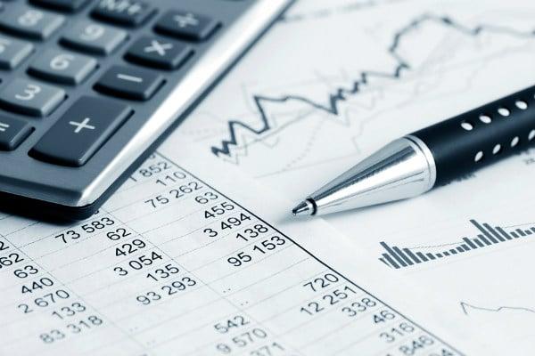 Unos papeles, bolígrafo y calculadora sobre una mesa de nuestra asesoría fiscal en Granada